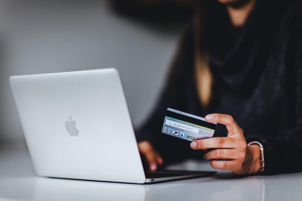クレジットカードを持ってパソコン画面を見ている人