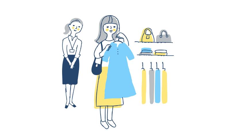 服を選んでいる女性と後ろにいる店員